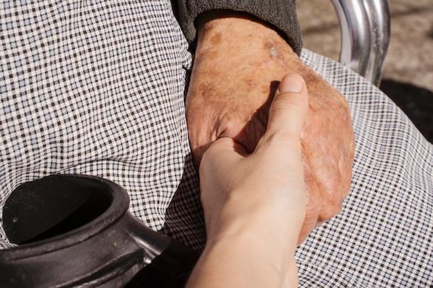 Mujer joven irreconocible con la mano de su abuela con cuidado. amor al concepto de personas mayores. personas con discapacidad en el estilo de vida de hogar de ancianos. casa de retiro para personas en situación geriátrica. Foto Premium