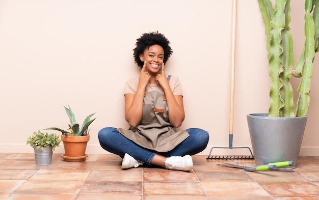 Mujer joven jardinero sentada en el suelo Foto Premium