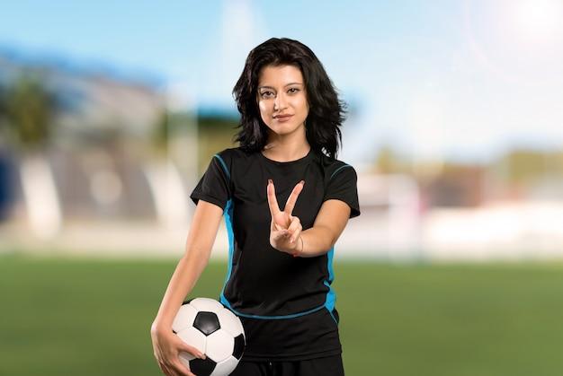 Mujer joven del jugador de fútbol que sonríe y que muestra la muestra de la victoria en al aire libre Foto Premium