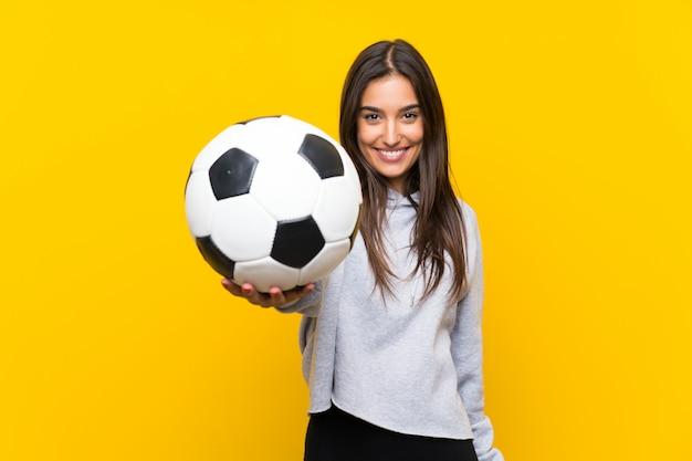 Mujer joven jugador de fútbol sobre pared amarilla aislada Foto Premium
