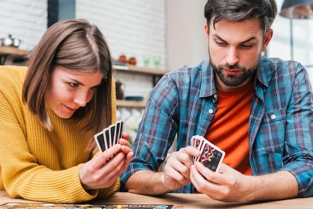 Mujer joven jugando a las cartas en casa Foto gratis
