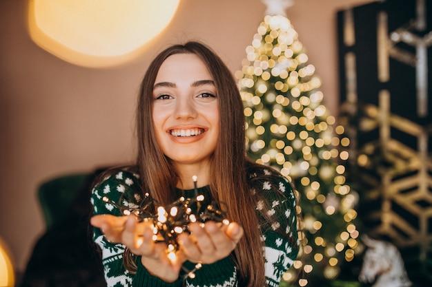 Mujer joven junto al árbol de navidad con luces brillantes de navidad Foto gratis