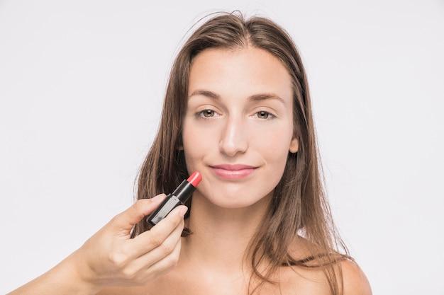 Mujer joven con lápiz labial Foto gratis
