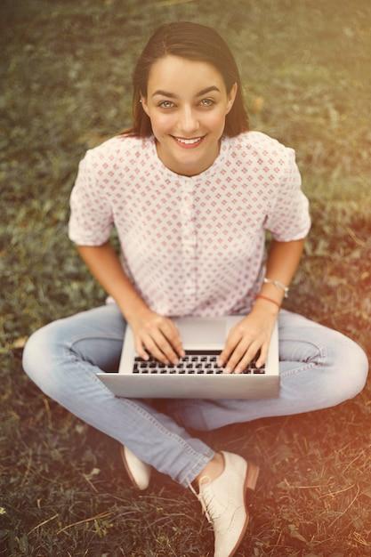 Mujer joven con laptop sentada sobre la hierba verde Foto gratis