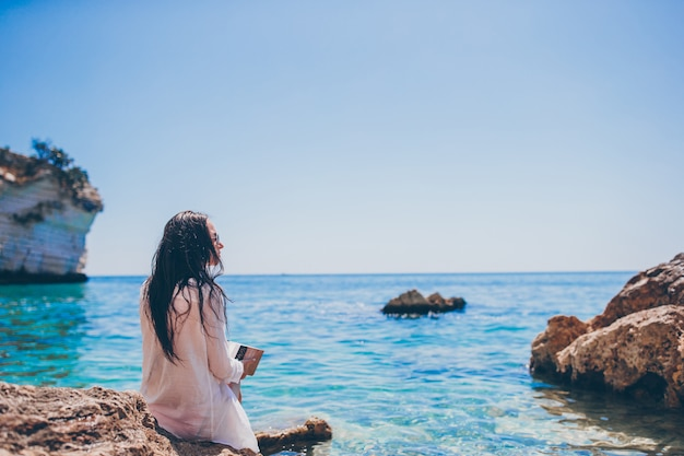 Mujer joven, lectura, en, tropical, playa blanca Foto Premium