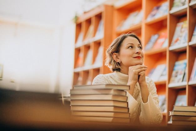 Mujer joven leyendo en la biblioteca Foto gratis