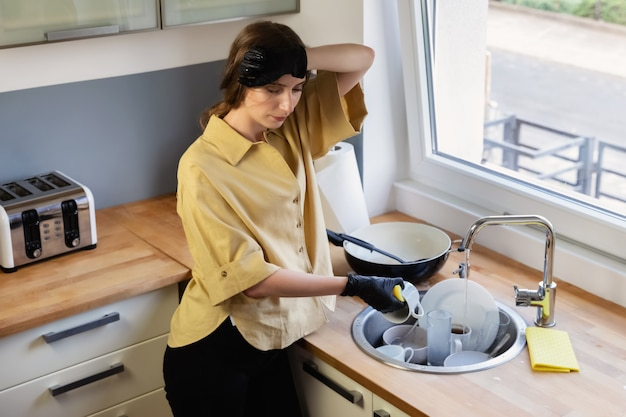 Una mujer joven se limpia en la cocina, lavando platos. está cansada y no está satisfecha con el hecho de que necesita hacerlo. Foto Premium