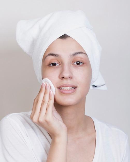 Mujer joven limpieza proceso facial Foto gratis