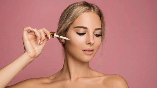 Mujer joven con maquillaje pipeta Foto gratis
