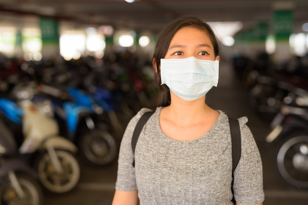 Mujer joven con máscara pensando en el estacionamiento Foto Premium