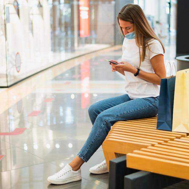 Mujer joven con mascarilla comprobación de teléfono móvil Foto gratis