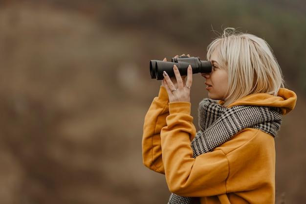 Mujer joven mirando con binoculares Foto gratis