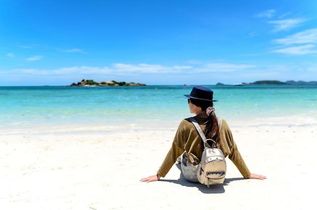 2f8590d2e Mujer joven con la mochila que se sienta en la playa solitaria y que ...