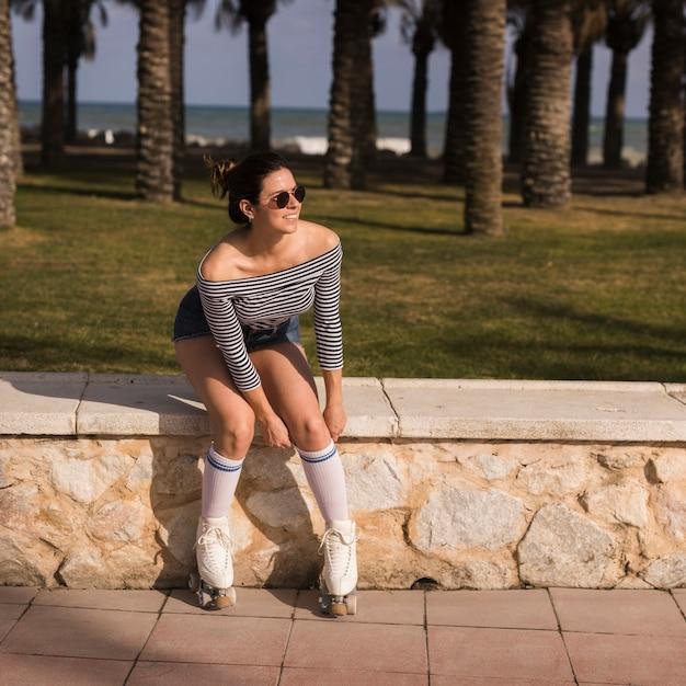 Mujer joven de moda sonriente que se sienta cerca de la playa Foto gratis