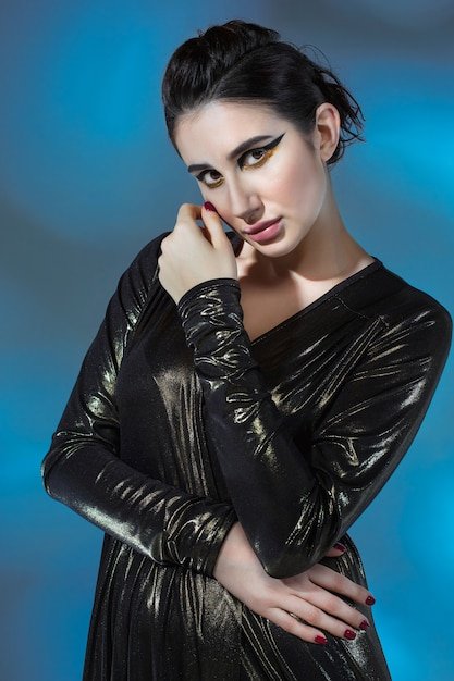 Mujer joven de moda en vestido negro con estilo. modelo glamour en pose de moda, maquillaje elegante Foto gratis