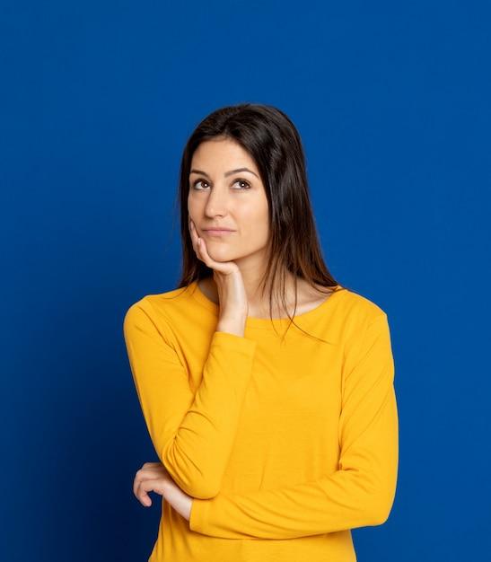 Mujer joven morena que gesticula sobre la pared azul Foto Premium