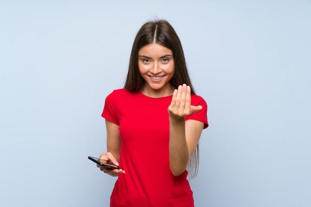 Mujer joven morena con un teléfono móvil sobre la pared azul aislada que invita a venir con la mano. Foto Premium
