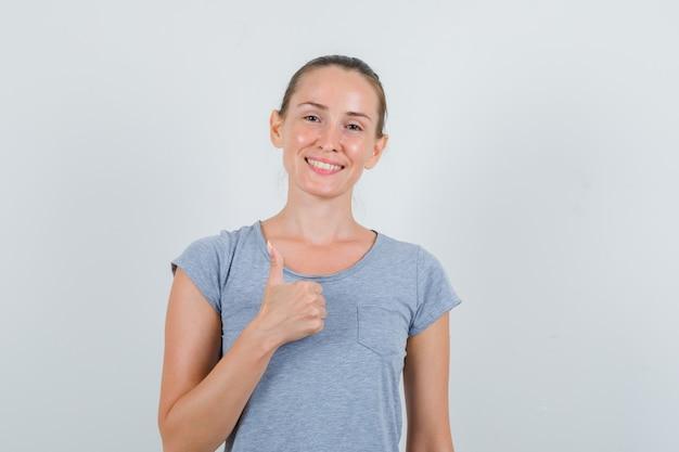 Mujer joven mostrando el pulgar hacia arriba en camiseta gris y mirando feliz, vista frontal. Foto gratis