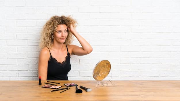 Mujer joven con mucho pincel de maquillaje en una mesa con dudas y con expresión de la cara confusa Foto Premium