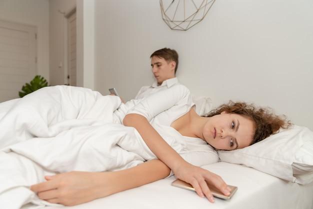 Mujer joven de los pares que siente la mentira triste en cama después de pelea con su boylfriend Foto Premium