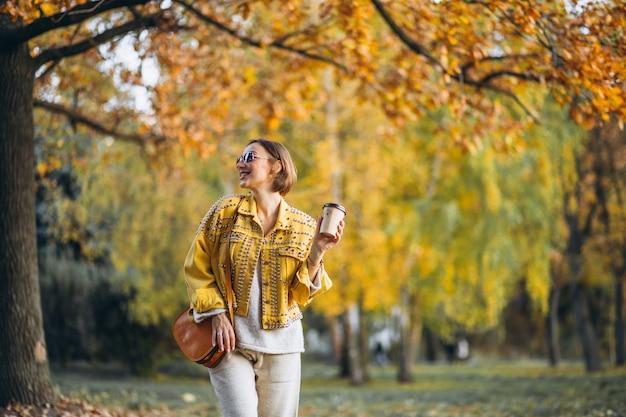 Mujer joven en un parque de otoño tomando café Foto gratis