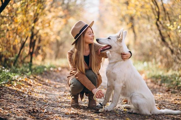 Mujer joven en el parque con su perro blanco Foto gratis