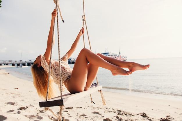 Mujer joven pasándolo bien en el columpio Foto gratis