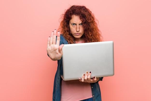 Mujer joven pelirroja caucásica sosteniendo una computadora portátil de pie con la mano extendida que muestra la señal de stop, impidiéndole. Foto Premium
