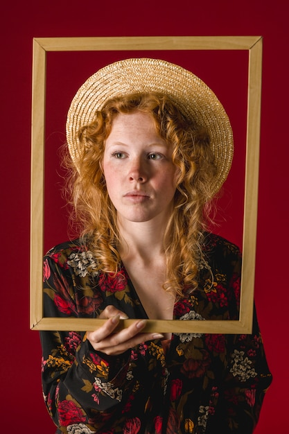 Mujer joven pelirroja con marco de madera Foto gratis