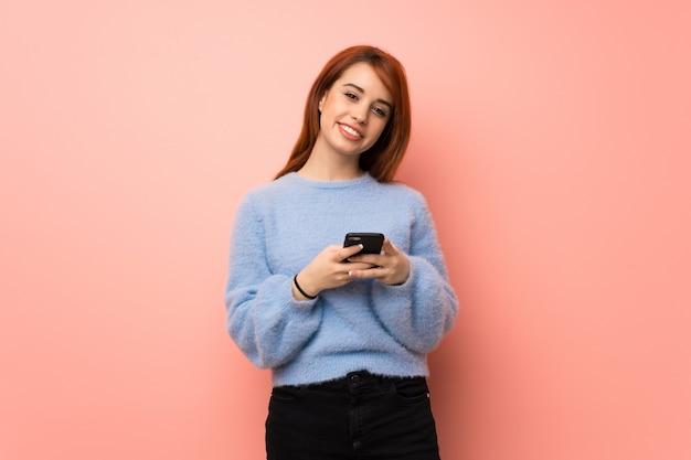 Mujer joven pelirroja sobre rosa enviando un mensaje con el móvil Foto Premium