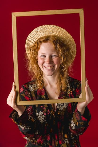 Mujer joven pelirroja sonriendo y sosteniendo el marco de madera Foto gratis