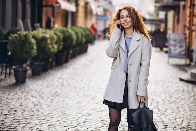 Mujer joven con pelo rizado usando el teléfono en la calle Foto gratis