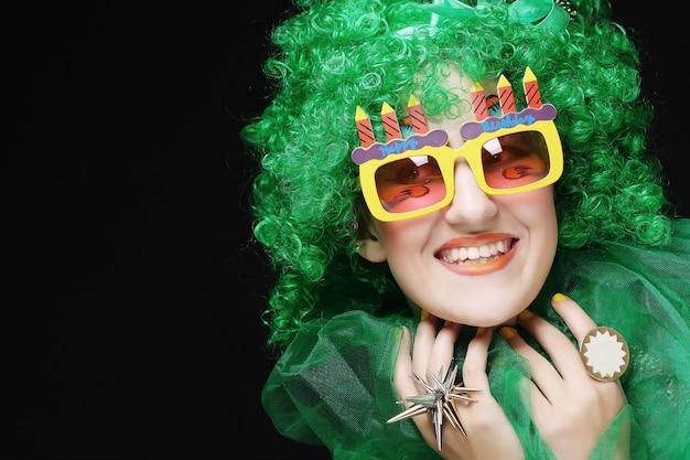Mujer joven con pelo verde y gafas de carnaval Foto Premium