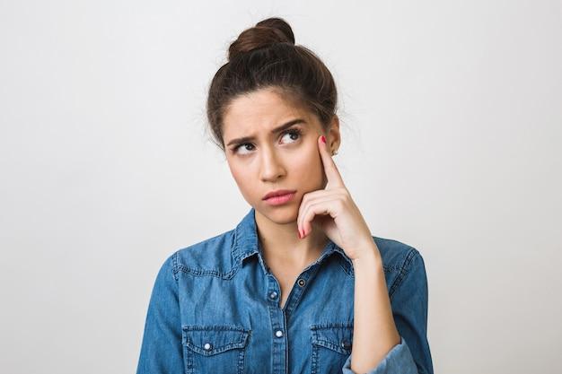 Mujer joven pensando, sosteniendo el dedo en su sien, mirando hacia arriba, elegante camisa de mezclilla, Foto gratis