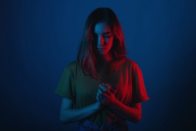 La mujer joven está de pie con la cabeza hacia abajo y las manos juntas. Foto Premium