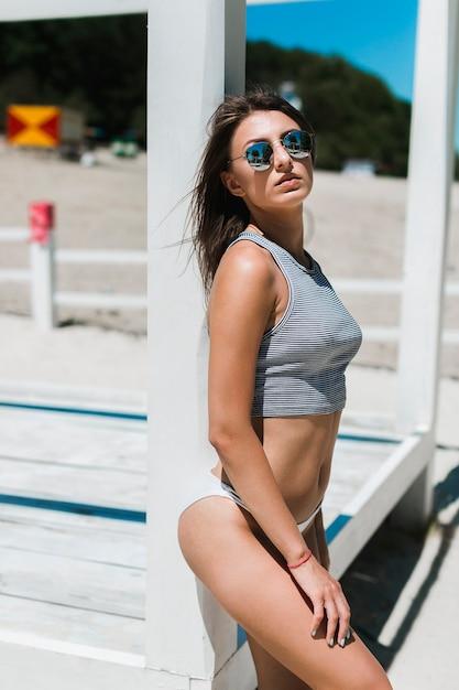 ed3fe5733db3 Mujer joven de pie cerca del pabellón de la playa | Descargar Fotos ...