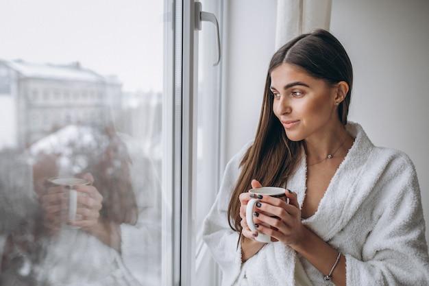 Mujer joven de pie junto a la ventana tomando café caliente Foto gratis
