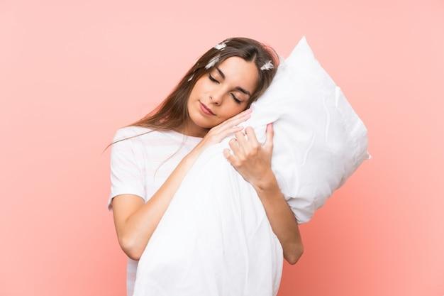 Mujer joven en pijama sobre pared rosa Foto Premium