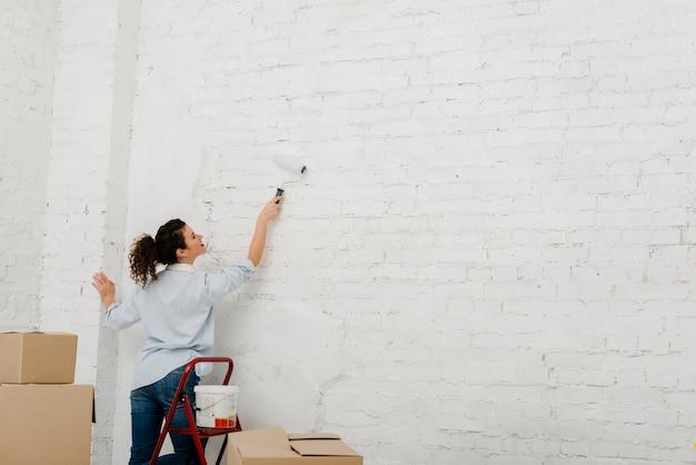 Mujer joven pintando la pared Foto Gratis