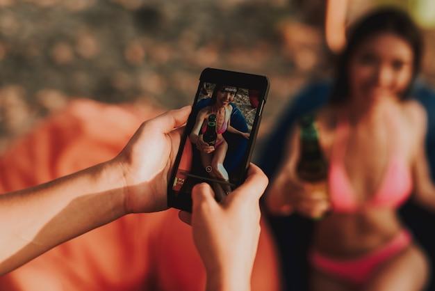 Mujer joven en poses del traje de baño para la foto en la playa. Foto Premium