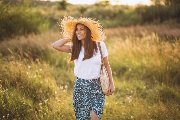 Mujer joven, posición, con, bolsa, en, sombrero grande, en, campo Foto gratis