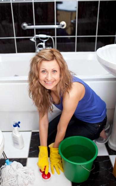 Mujer joven positiva que limpia el piso del cuarto de baño ...