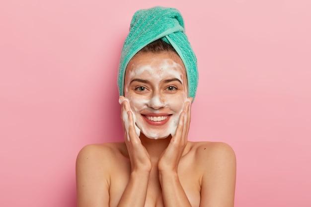 Mujer joven positiva tiene una sonrisa con dientes, tiene dientes perfectos, acaricia la piel con jabón líquido sanitario, se lava con gel espumoso, se despierta por la mañana para tener una rutina de belleza Foto gratis