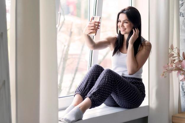Mujer joven positiva tomando un selfie Foto gratis