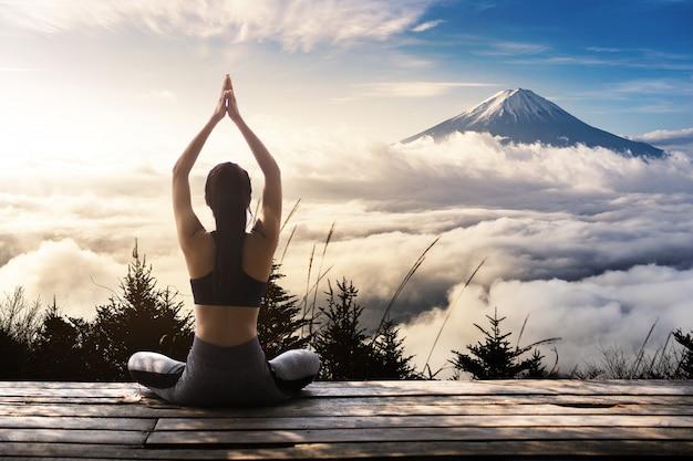 Mujer joven practicando yoga en la naturaleza Foto Premium