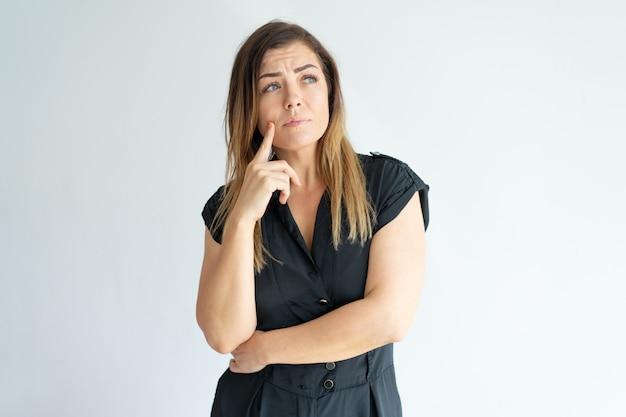 Mujer joven preocupada pensativa perdida en pensamientos y mirando lejos. Foto gratis