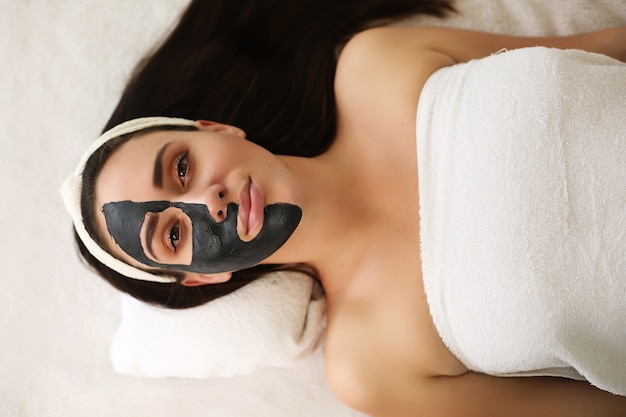 Mujer joven con procedimiento de máscara en el centro de spa Foto Premium
