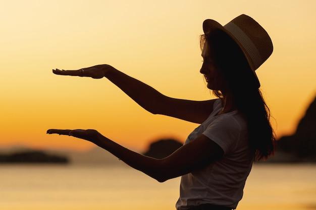 Mujer joven y puesta de sol en el fondo Foto gratis