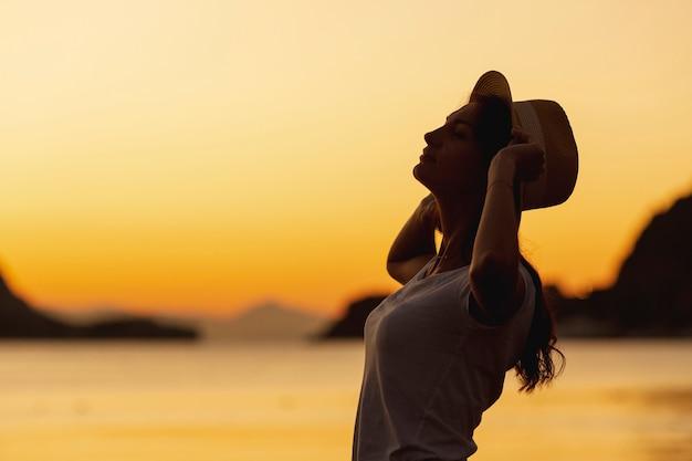 Mujer joven y puesta de sol en la orilla de un lago Foto gratis