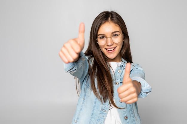 Mujer joven con los pulgares arriba aislado sobre una pared blanca Foto gratis